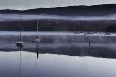 在一个湖的早晨薄雾有小船的 库存照片