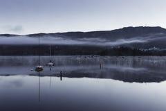 在一个湖的早晨薄雾有小船的 免版税库存照片