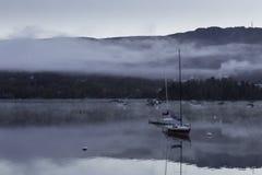 在一个湖的早晨薄雾有小船的 免版税库存图片