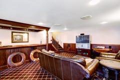 有酒吧和富有的皮革家具集合的豪华家庭娱乐室 免版税库存照片