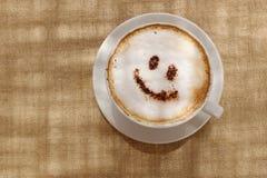 与泡沫或巧克力微笑的受欢迎的愉快的面孔的咖啡热奶咖啡 免版税库存照片