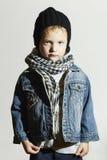 围巾和牛仔裤的时兴的小男孩 冬天样式 方式孩子 黑盖帽的孩子 免版税图库摄影