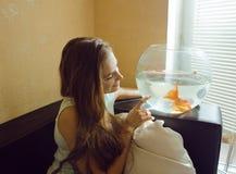 在家使用与金鱼的俏丽的妇女 免版税图库摄影