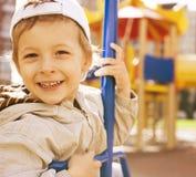 外面摇摆的小逗人喜爱的男孩,操场 免版税图库摄影