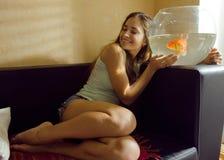 在家使用与金鱼的俏丽的妇女 免版税库存照片