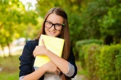 有玻璃和书的青少年的女孩 免版税图库摄影