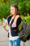 有书和一个背包的青少年的学生女孩在手上 免版税库存图片