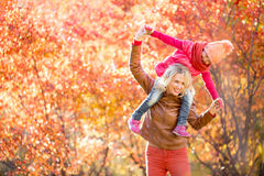 愉快的母亲和孩子获得室外的乐趣一起在秋天 免版税图库摄影