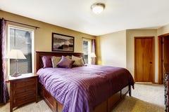 有明亮的紫色卧具的豪华卧室家具 库存照片