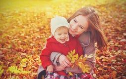 愉快的家庭:母亲和儿童小女儿演奏拥抱秋天 库存照片