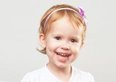 笑和微笑在灰色背景的美丽的愉快的小女孩 库存照片