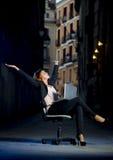 年轻愉快的女商人坐在街道上的办公室椅子有膝上型计算机的 免版税图库摄影