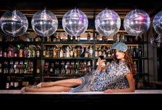 说谎在酒吧的性感的少妇在夜迪斯科俱乐部 免版税库存照片