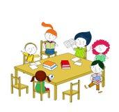 孩子写并且读,坐在桌上 免版税库存图片