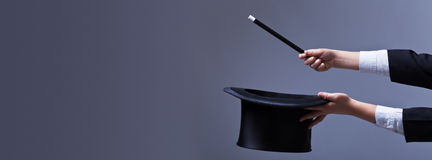 Χέρια μάγων με το καπέλο και τη μαγική ράβδο Στοκ Φωτογραφίες