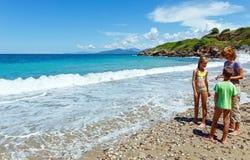 在夏天海滩(希腊,莱夫卡斯州)的家庭 免版税库存图片