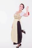 少女装的年轻巴法力亚妇女拿着与一个手指的一个小小包在肩膀 免版税库存照片