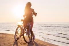 时髦的女人在海滩的骑马自行车在日落 库存照片