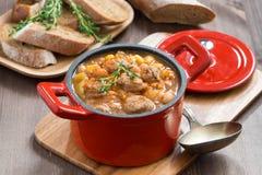 可口菜炖煮的食物用在一个红色平底锅的香肠 免版税库存照片