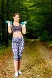 Молодая женщина делая протягивающ тренировку на лесе дороги Стоковое Фото