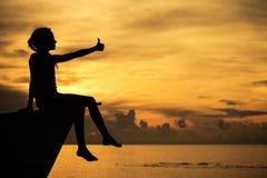 愉快的青少年的女孩坐海滩 免版税图库摄影