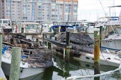 火在小游艇船坞的被烧的小船事故 免版税库存照片