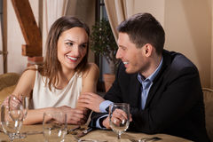 微笑的夫妇等待的晚餐在餐馆 免版税库存图片
