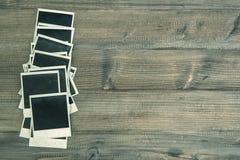 Εκλεκτής ποιότητας στιγμιαία πλαίσια φωτογραφιών στο αγροτικό ξύλινο υπόβαθρο Στοκ Εικόνα