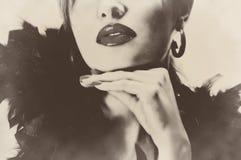 有黑羽毛的性感的相当美丽的妇女,发光的嘴唇乌贼属减速火箭的葡萄酒 免版税库存图片