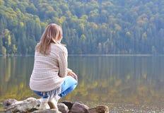 放松在湖附近的美丽的少妇 免版税库存图片