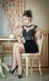 坐在餐馆的黑礼服的时兴的可爱的少妇 美好深色摆在典雅的葡萄酒风景 免版税图库摄影