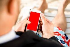 拿着在海滩的商人手机 库存图片