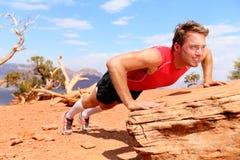 健身运动员训练俯卧撑本质上 免版税库存图片