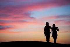 现出轮廓的夫妇观看的日落天空 免版税库存照片