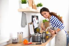 少妇在准备食物的厨房里 图库摄影
