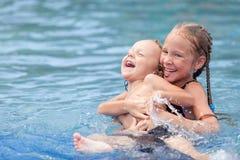 使用在游泳池的兄弟和姐妹 免版税库存图片