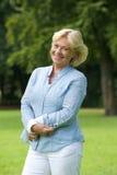 微笑在公园的愉快的资深妇女 免版税库存照片