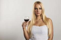 有葡萄酒杯的美丽的白肤金发的女孩 干红葡萄酒 有酒精的性感的少妇 这里您的文本 库存照片
