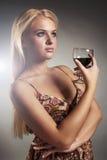 礼服的美丽的白肤金发的妇女用酒 干红葡萄酒 有酒精的性感的少妇 免版税库存照片