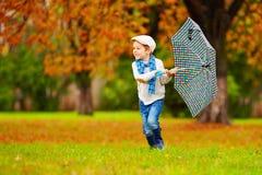 享用秋天雨的愉快的男孩在公园 免版税库存照片