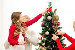Χαμογελώντας οικογένεια που διακοσμεί το χριστουγεννιάτικο δέντρο στο σπίτι Στοκ φωτογραφίες με δικαίωμα ελεύθερης χρήσης
