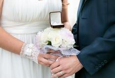 拿着与金黄圆环的新娘和新郎婚礼花束 免版税库存图片