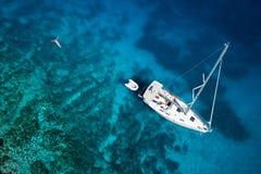 对游艇、游泳的妇女和清楚的水加勒比的惊人的看法 免版税库存照片