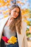Σκεπτική νέα γυναίκα με τα φύλλα φθινοπώρου Στοκ εικόνες με δικαίωμα ελεύθερης χρήσης