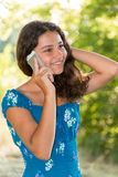 有一个电话的青少年的女孩在公园 免版税图库摄影