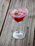红色夏天马蒂尼鸡尾酒饮料用在木的薄菏 免版税库存照片