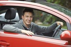 坐在汽车的最近合格的十几岁的男孩司机 免版税库存照片