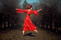 红色礼服的女孩腾飞 免版税库存图片