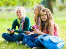 获得少年的女小学生与手机的乐趣 免版税库存图片