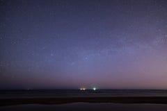 与星的夜空在海滩 蓝色展望期少校编号安排了行星空间范围视图 免版税库存图片
